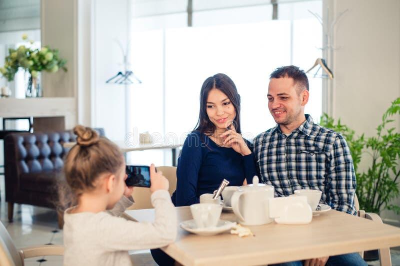 Família, paternidade, conceito dos povos da tecnologia - próximo acima da mãe feliz, pai e menina que têm o jantar, criança imagem de stock