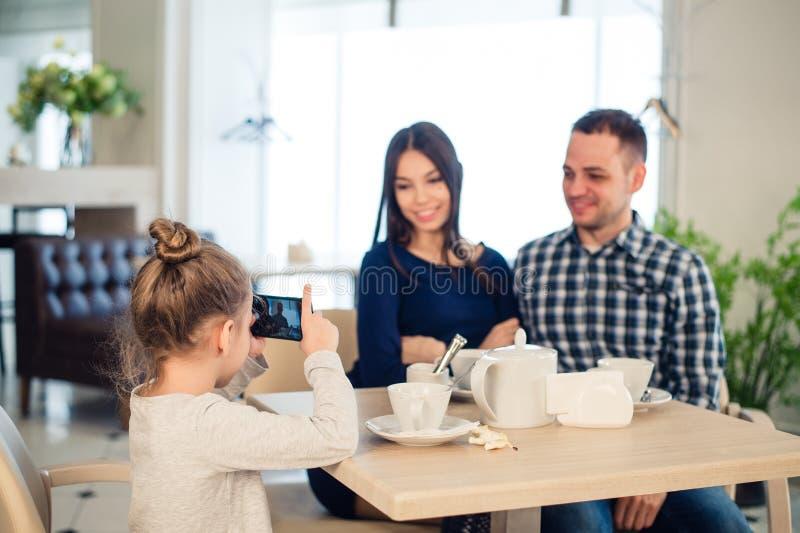 Família, paternidade, conceito dos povos da tecnologia - próximo acima da mãe feliz, pai e menina que têm o jantar, criança fotografia de stock