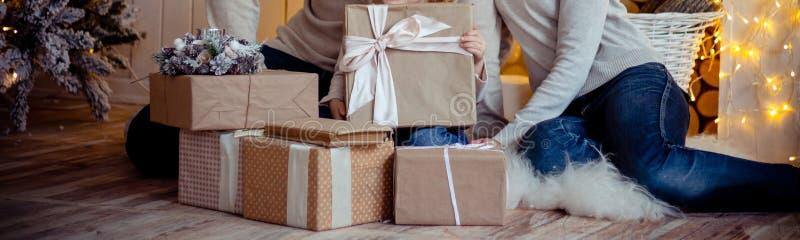 A família perto da árvore de Natal, abraça e mantém presentes, mamã, paizinho e filha, uma criança Manhã de Natal, véspera do ` s fotografia de stock