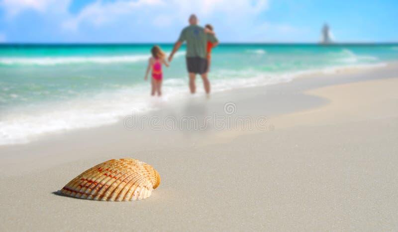 Família por Seashell na praia tropical imagem de stock