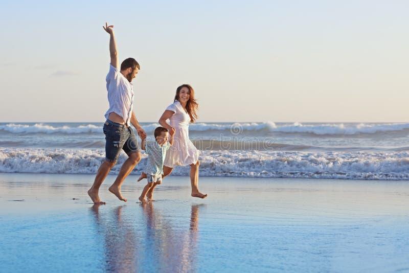 Família positiva que corre ao longo da borda do mar na praia foto de stock royalty free