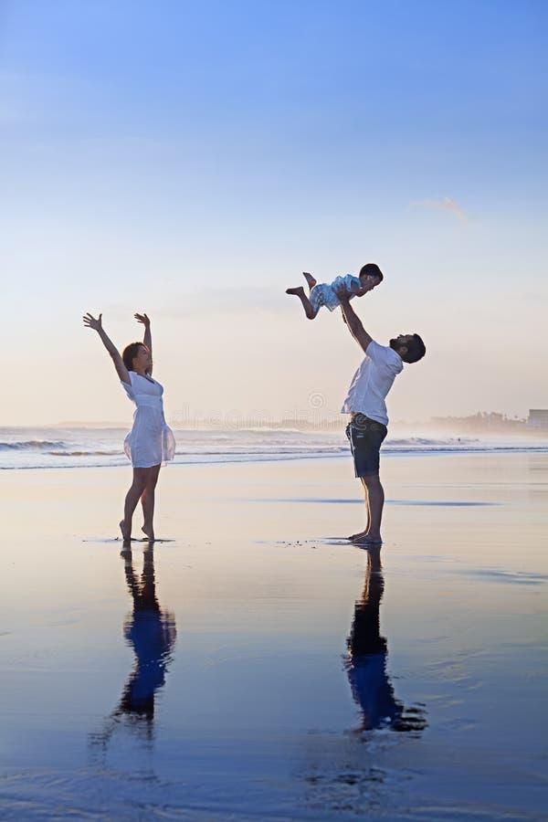 Família positiva que tem o divertimento na praia preta do mar da areia imagem de stock