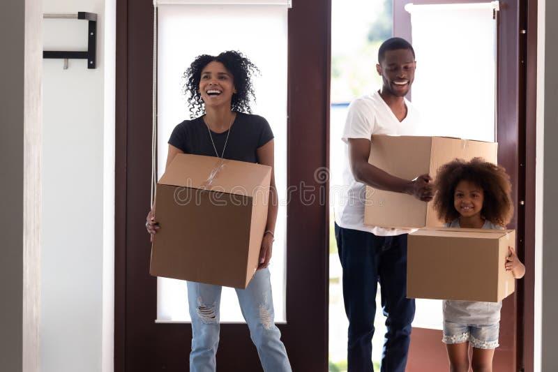 Família preta entusiasmado que entra na casa nova que guarda as caixas que movem-se dentro foto de stock