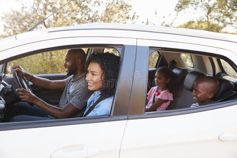 Família preta nova em um sorriso do carro na viagem por estrada imagem de stock
