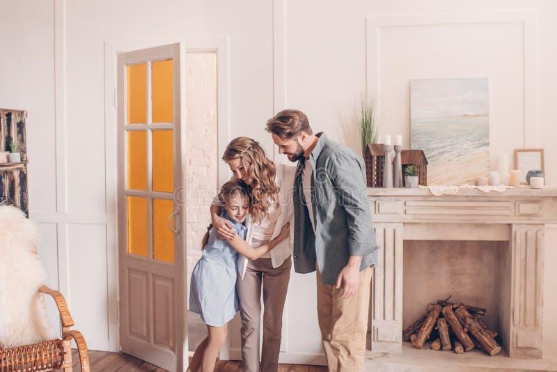 Família que abraça e que está em casa com chaminé atrás fotos de stock royalty free