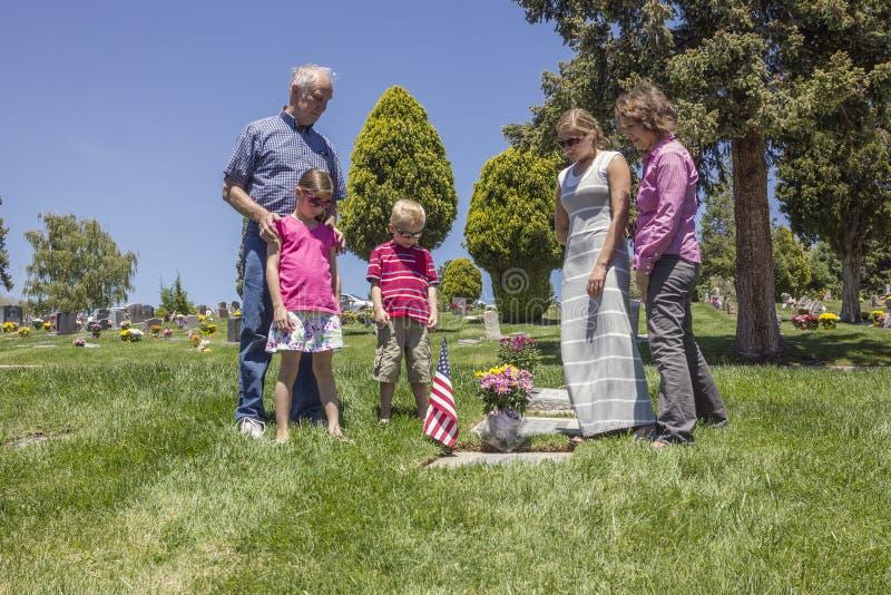 Família que aflige-se junto em uma sepultura em um cemitério fotos de stock royalty free