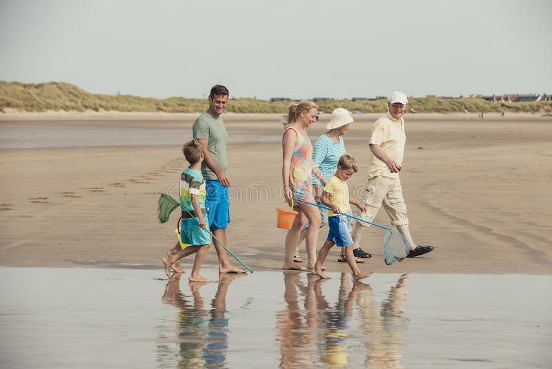 Família que anda à parte dianteira de mar fotografia de stock