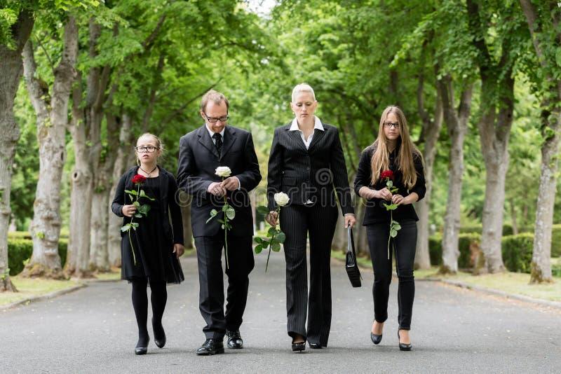 Família que anda abaixo da aleia no cemitério fotografia de stock