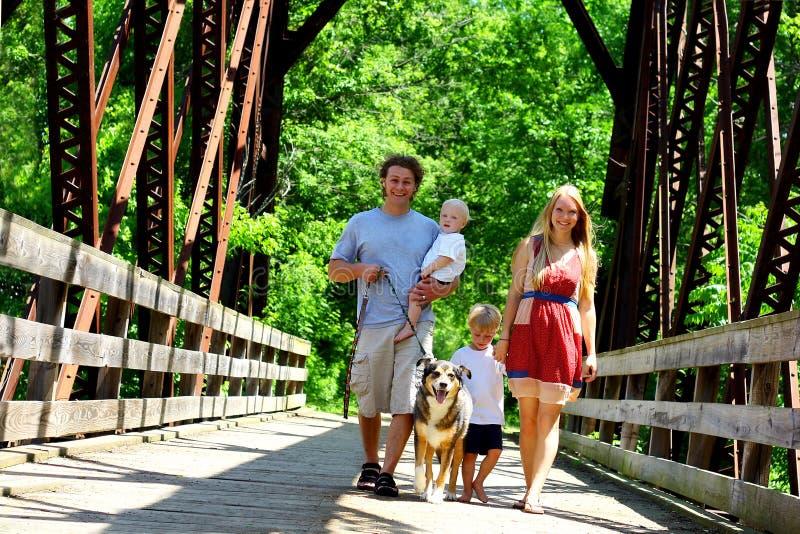 Família que anda através da ponte imagens de stock
