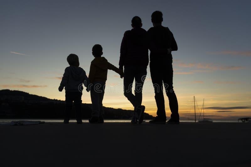 Família que anda fora no por do sol fotografia de stock