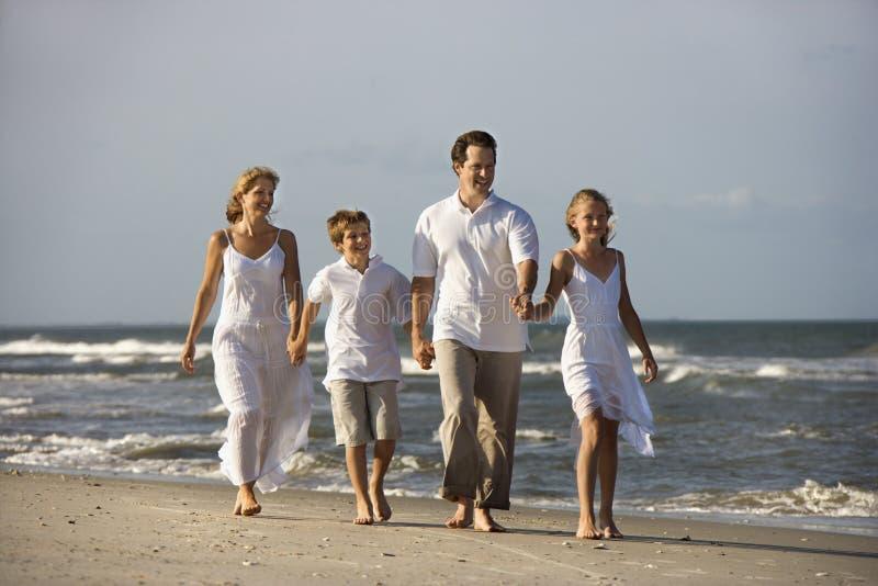 Família que anda na praia. foto de stock