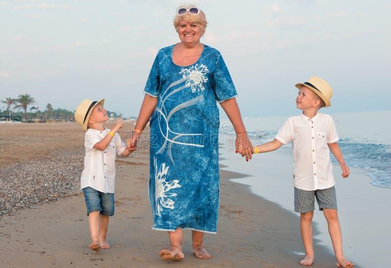 Família que anda na praia da noite durante o por do sol Avó e dois netos imagem de stock