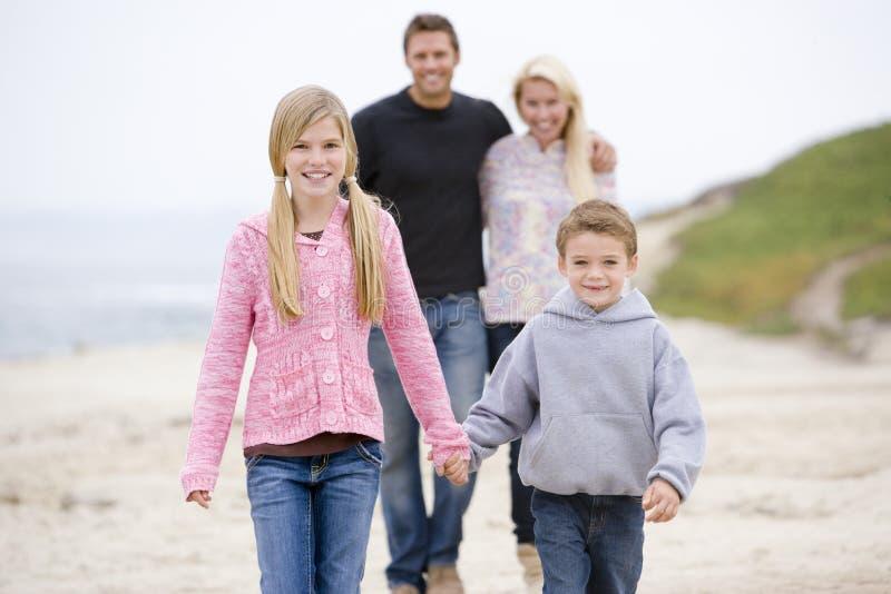 Família que anda nas mãos da terra arrendada da praia foto de stock