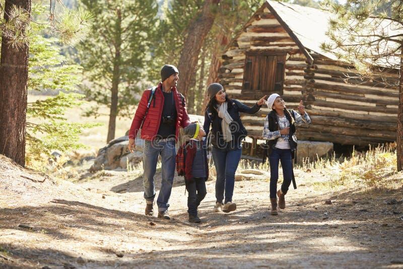 Família que anda no trajeto de floresta após uma cabana rústica de madeira imagens de stock royalty free