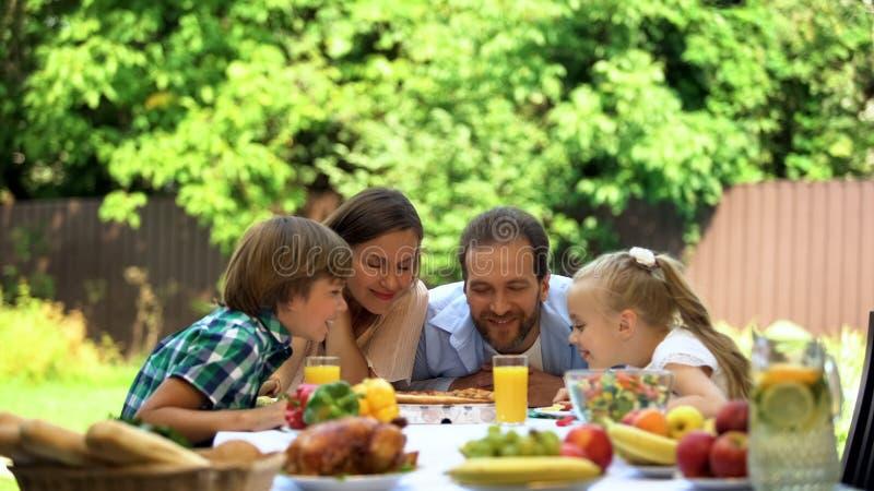 Família que aprecia o cheiro da pizza perfumada, culinária italiana, serviço de entrega do alimento imagens de stock