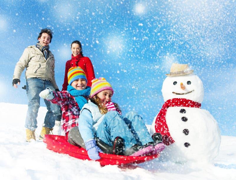 Família que aprecia o conceito de Tobogganing do dia de inverno imagens de stock royalty free