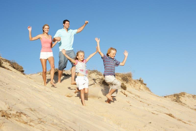 Família que aprecia o feriado da praia que funciona abaixo da duna