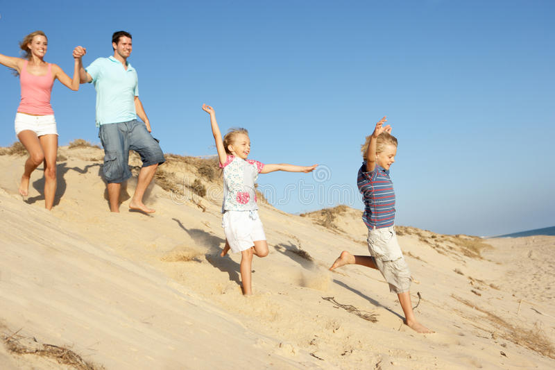 Família que aprecia o feriado da praia que funciona abaixo da duna imagens de stock