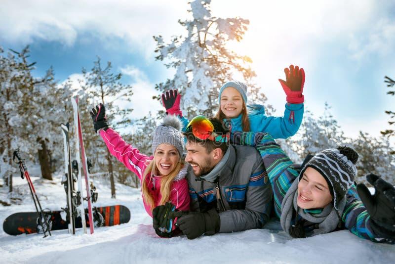 A família que aprecia o inverno vacations nas montanhas na neve imagem de stock royalty free