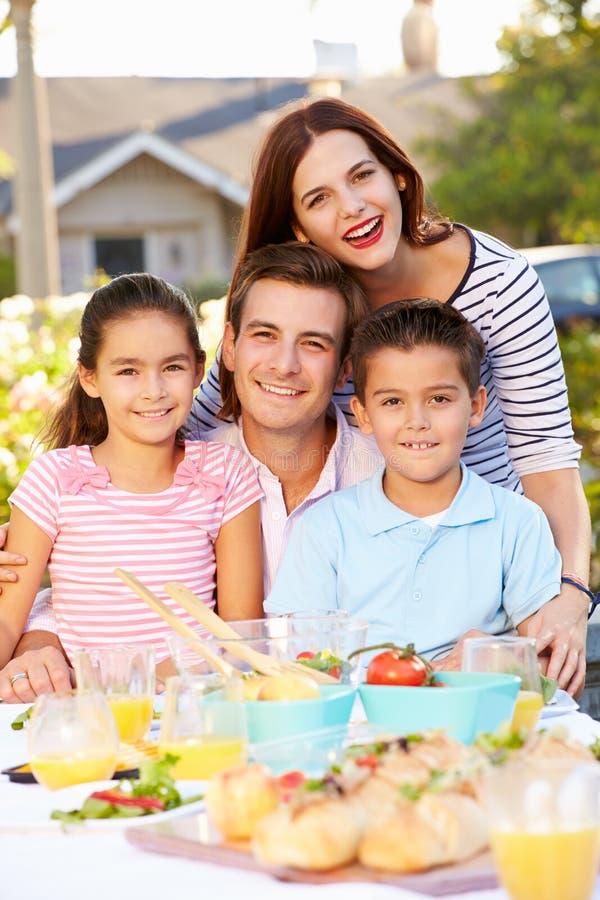 Família que aprecia a refeição exterior no jardim imagem de stock royalty free