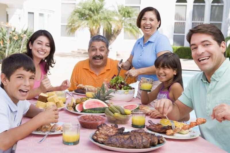 Família que aprecia um assado imagem de stock