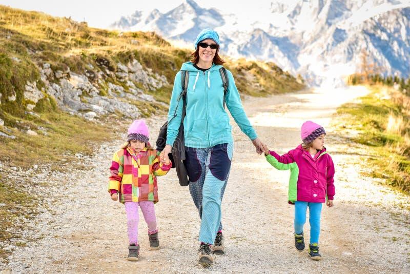 Família que caminha nas montanhas imagem de stock