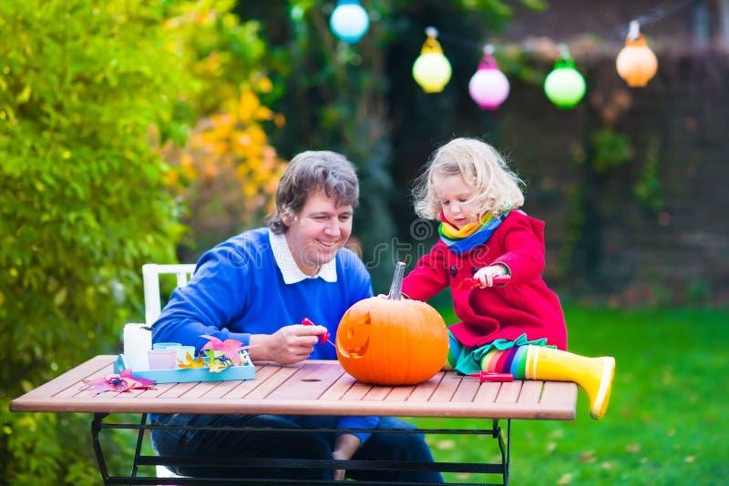 Família que cinzela a abóbora em Dia das Bruxas fotografia de stock