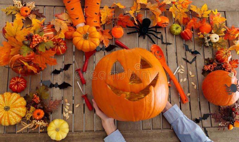 Família que cinzela a abóbora Truque ou deleite de Halloween imagem de stock royalty free