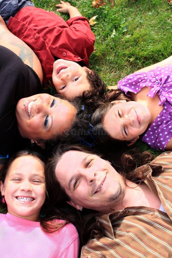 Família que coloca na grama fotos de stock royalty free