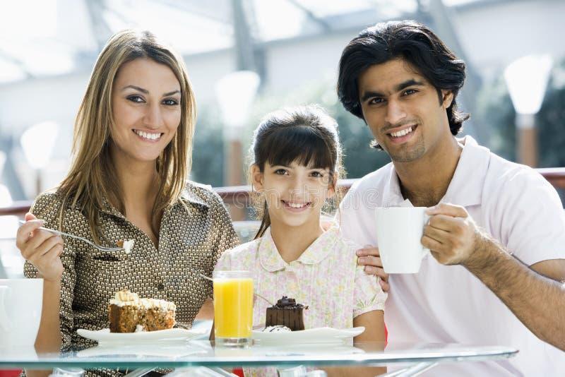 Família que come o bolo no café foto de stock royalty free