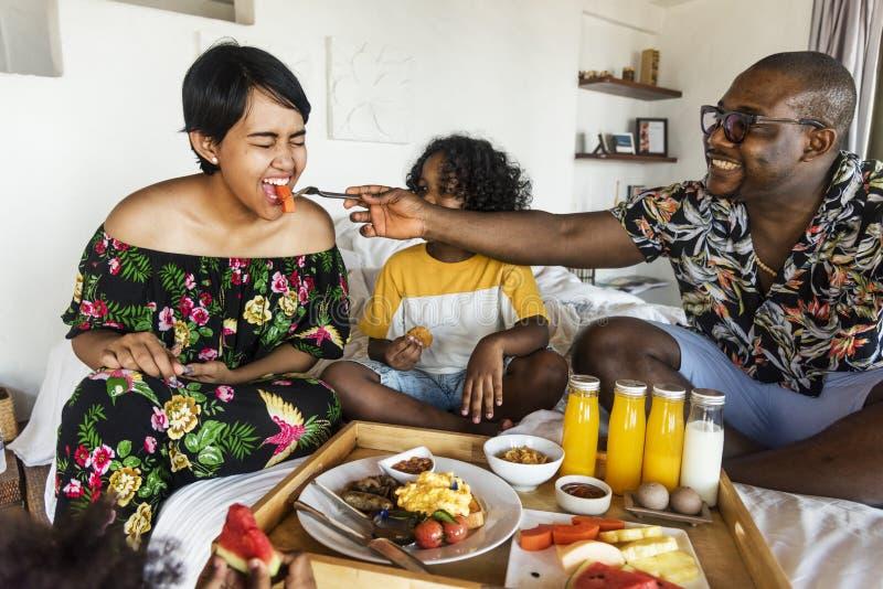 Família que come o café da manhã na cama fotos de stock