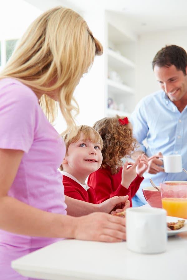 Família que come o café da manhã na cozinha antes da escola imagens de stock