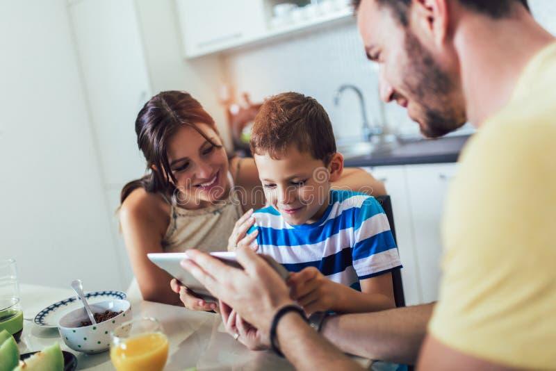 Família que come o café da manhã na mesa de cozinha e que usa a tabuleta digital imagem de stock royalty free