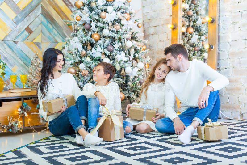 Família que comemora em casa o pai, a mãe e as crianças no fundo da árvore de Natal com presentes sentam-se no imagens de stock