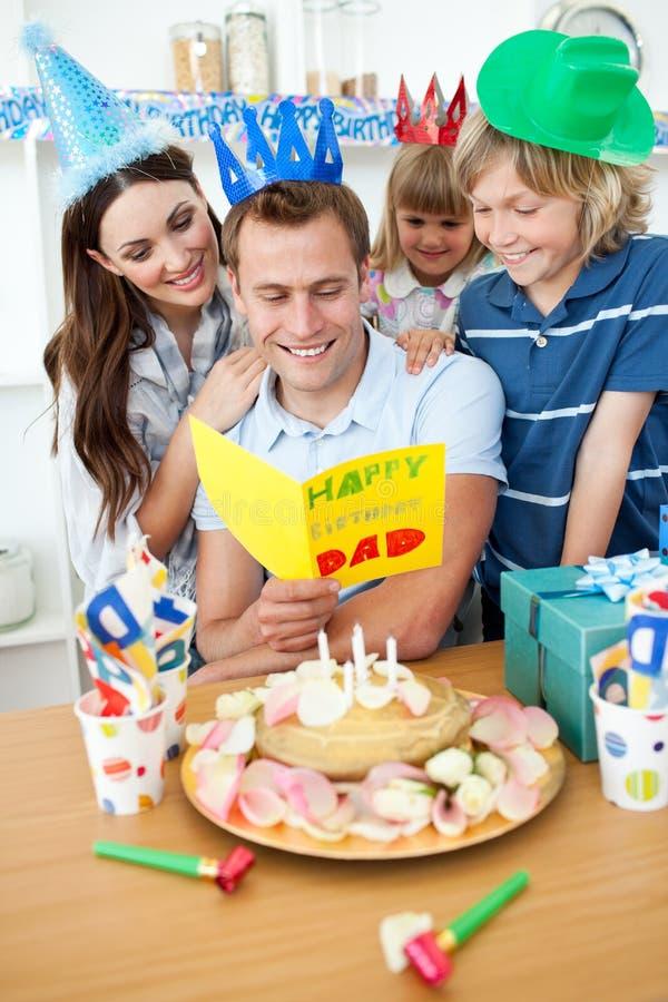 Família que comemora o aniversário do paizinho com bolo fotografia de stock