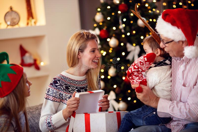 Família que compartilha do presente na mãe de sorriso do Natal que dá o presente fotos de stock