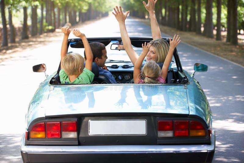 Família que conduz longitudinalmente em um carro de esportes imagem de stock