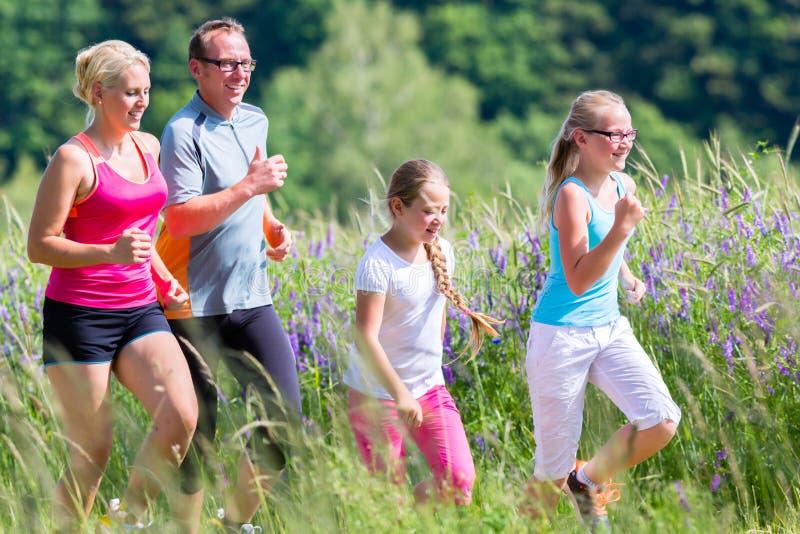 Família que corre para a melhor aptidão no verão imagem de stock