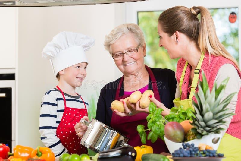 Família que cozinha no agregado familiar multigenerational com filho, mãe, imagem de stock royalty free