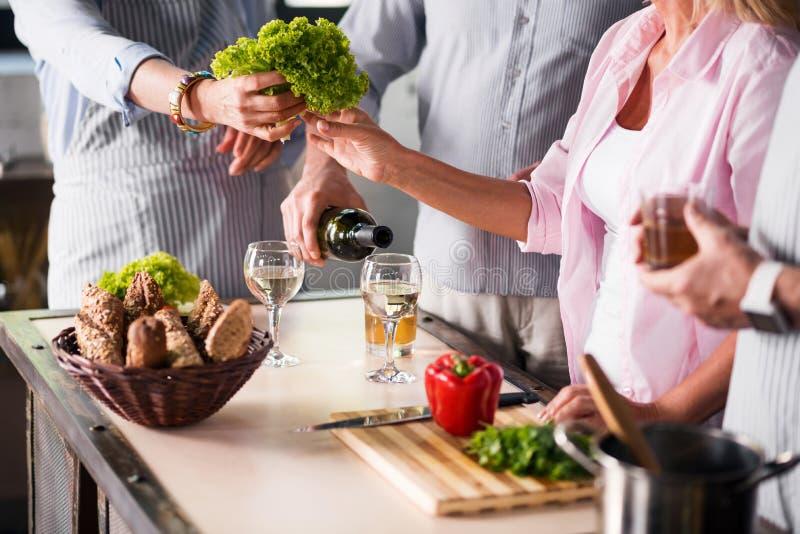 Família que cozinha o alimento junto ao apreciar o vinho fotografia de stock royalty free