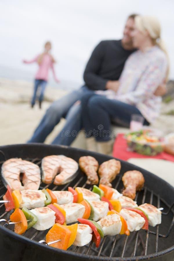 Família que cozinha o assado em uma praia