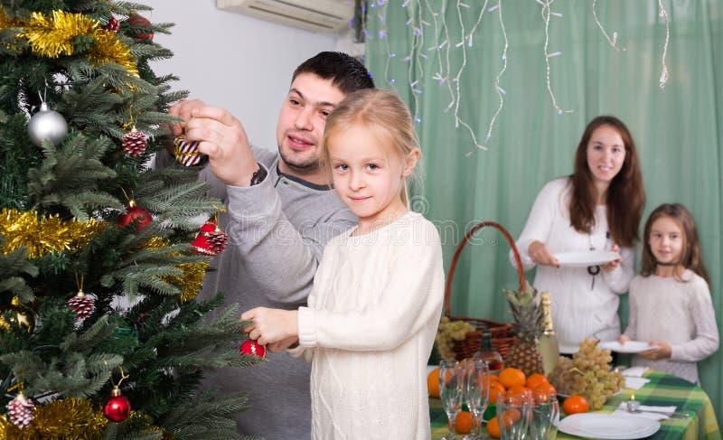Família que decora a árvore de Natal em casa foto de stock royalty free