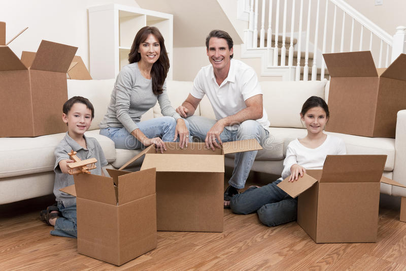 Família que desembala as caixas que movem a casa imagens de stock royalty free