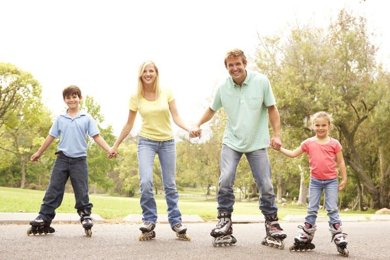 Família que desgasta na linha patins no parque fotografia de stock