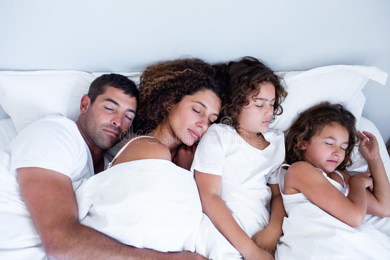 Família que dorme junto na cama foto de stock royalty free