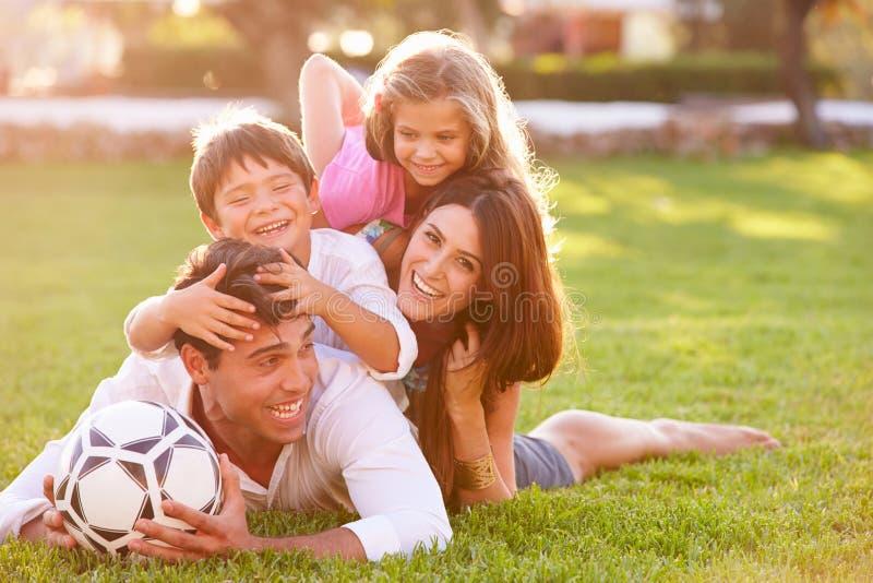 A família que encontra-se dentro empilha acima na grama junto foto de stock
