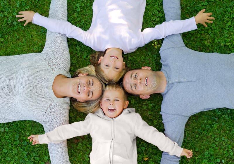 Família que encontra-se na grama e no sorriso imagens de stock