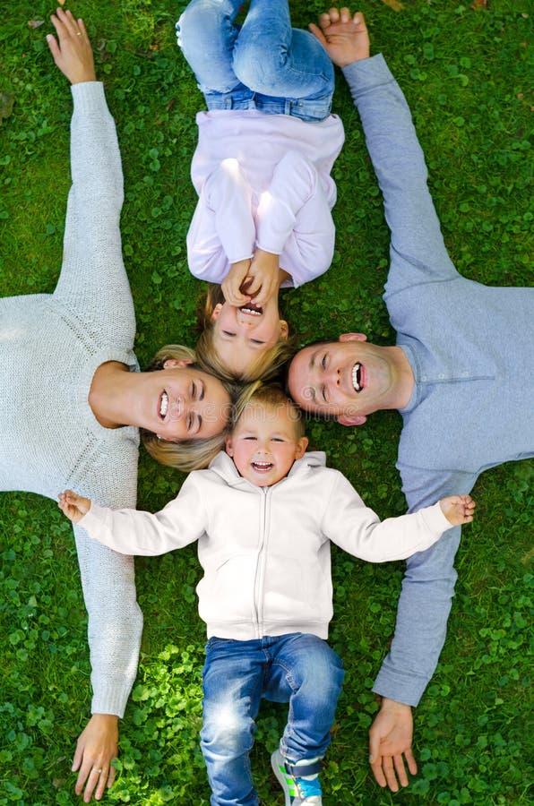 Família que encontra-se na grama e no sorriso imagens de stock royalty free