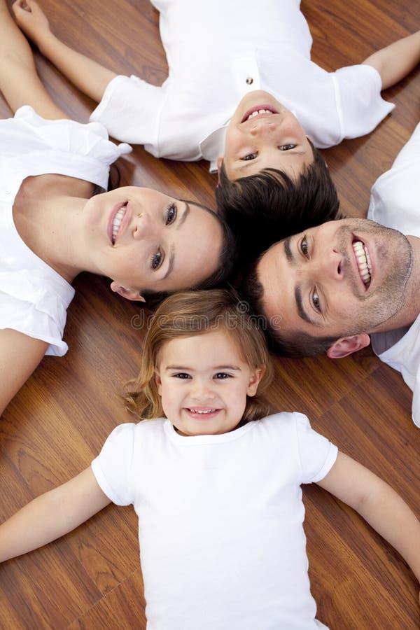 Família que encontra-se no assoalho com cabeças junto imagens de stock royalty free