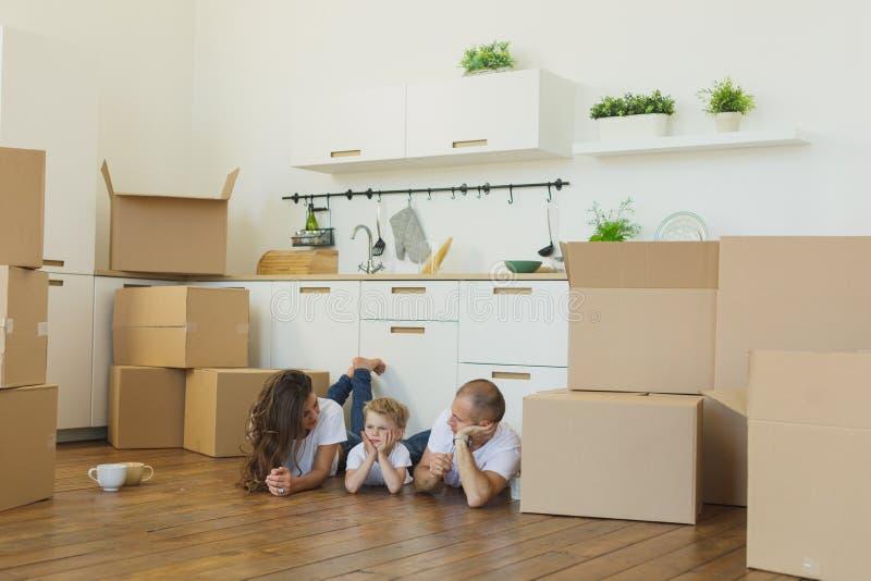 Família que encontra-se no assoalho por caixas abertas no sorriso home novo imagem de stock